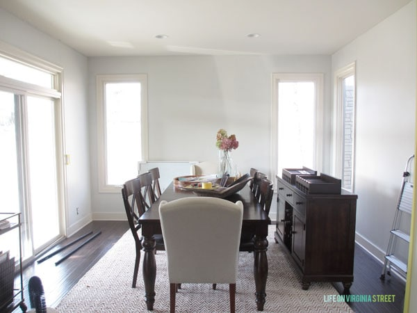 Dining room with bare walls to show off new coat of off-white paint.