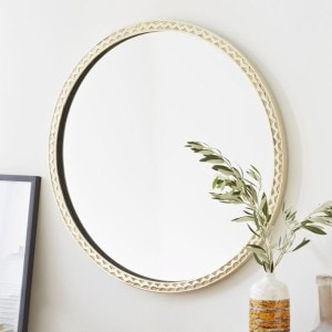 Look at the beautiful accents on this thin textured brass round mirror.