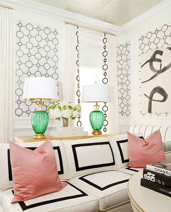 Black and white walls, green lamps and pink pillows in sitting room.