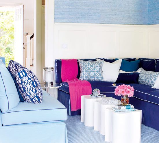 Cobalt blue couches with a bright pink throw and pink flowers in room.