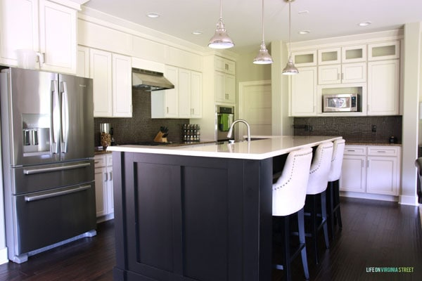 A large stainless steel fridge, a dark kitchen island with a white countertop and white cupboards.