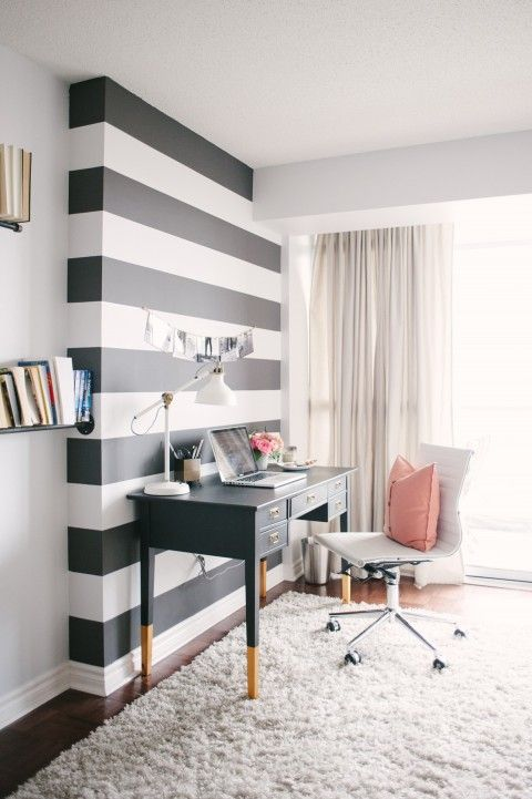 Black and white striped walls in office with a black desk in front of it and a white chair with a pink pillow on it.