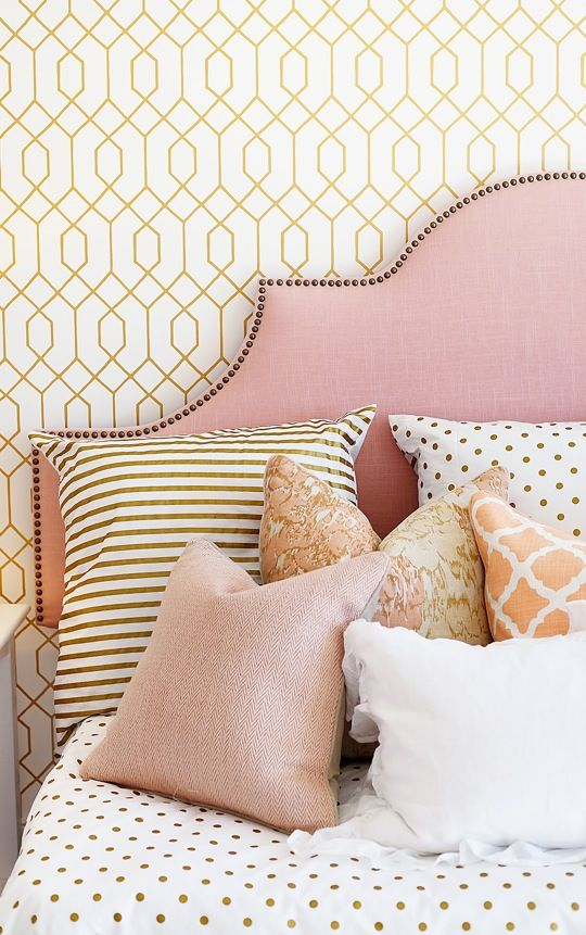 A bright pink headboard and pink pillows in a bedroom.