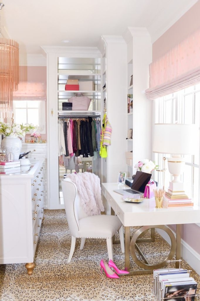 A dressing room with light pink shades, a pink throw on the chair and bright pink shoes on the floor.