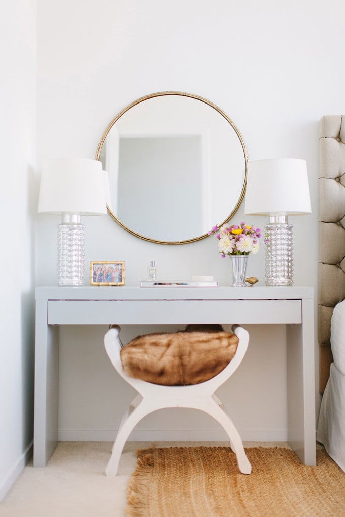 Beautiful round mirror above a vanity flanked with two crystal lamps with white shades.
