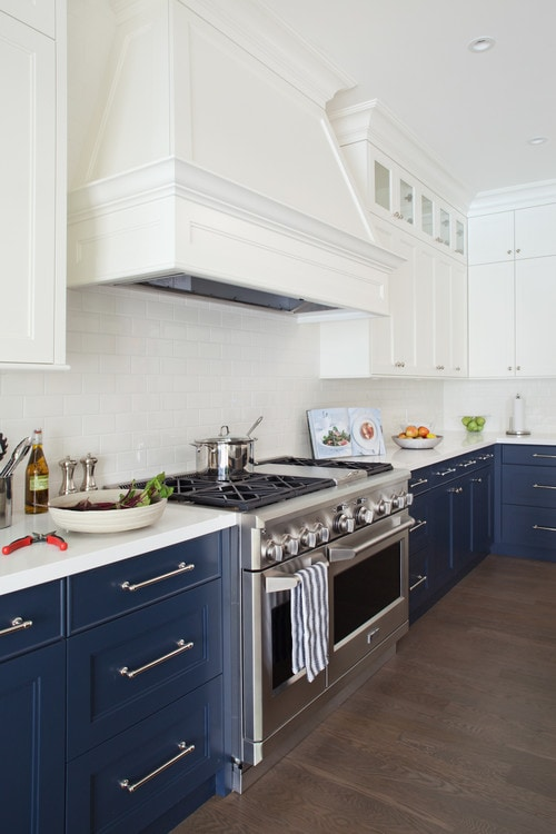 A white kitchen with blue bottom cupboards and silver handles.