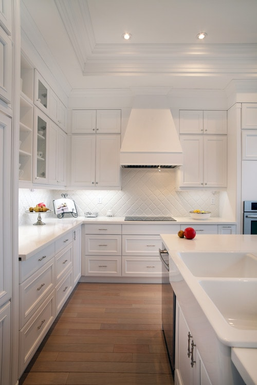 An all white kitchen with fruit on the counters.