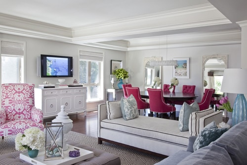 Bright pink dining chairs are echoed by the armchair in the livingroom, making this space pop but not overwhelm.