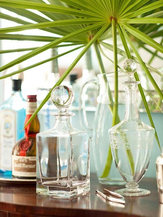 Decanters on top of a wood bar with palm fronds over top of it.