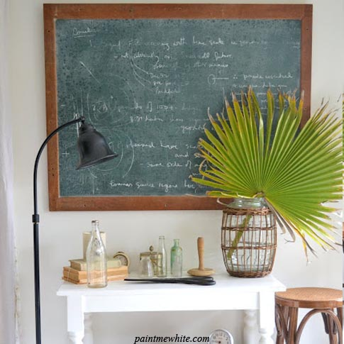 A white side table with a chalkboard above it and a palm frond on the table.