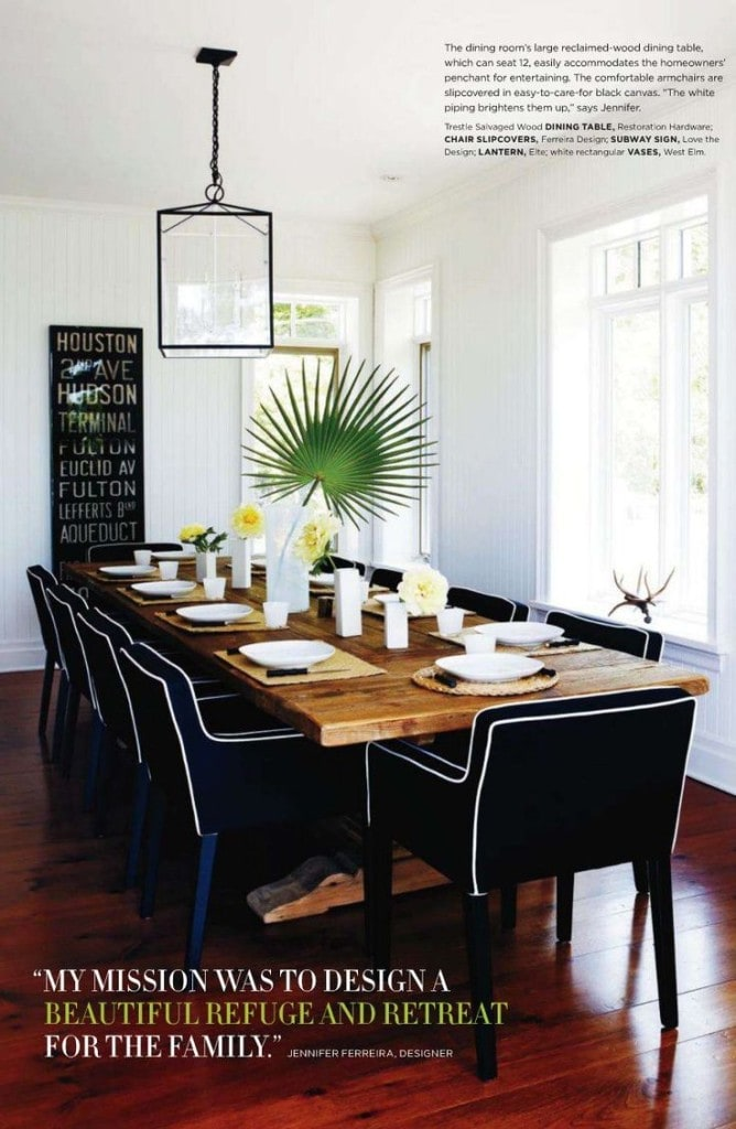 A wooden rustic table with navy blue chairs and a palm frond as the centrepiece.