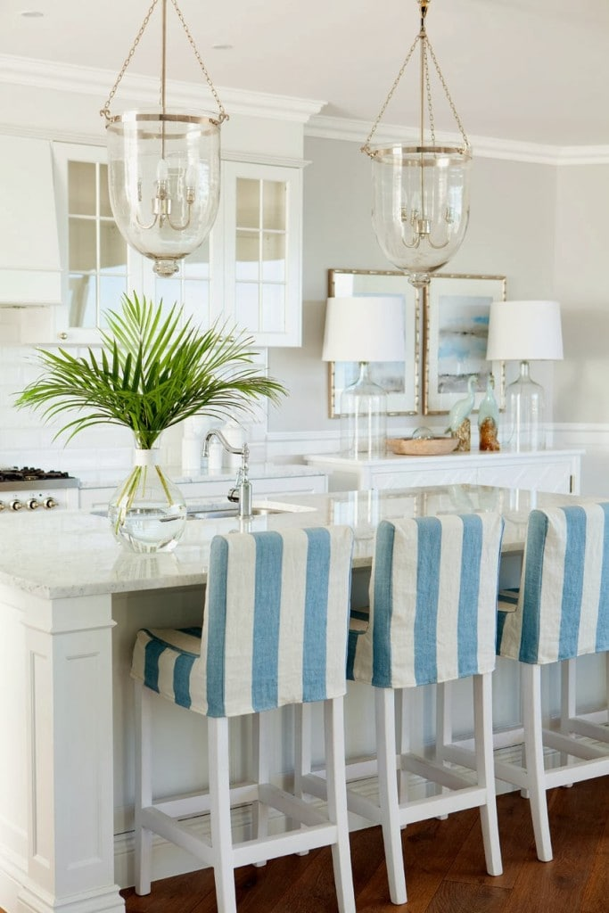 White kitchen with blue and white striped chairs and palm fronds on the island.