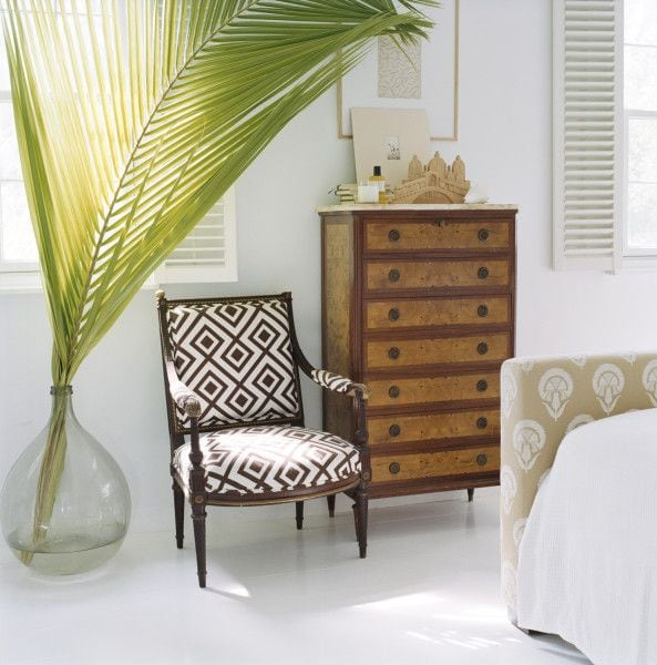 A large palm frond in a clear glass vase on the floor beside a chair and dresser.
