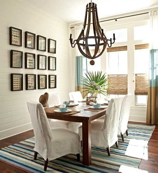 A coastal style dining room with a striped rug, white shiplap walls, wine barrel wood chandelier, palm fronds, gallery wall, woven shades and striped curtains.