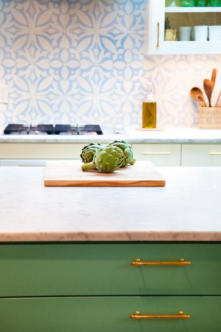 .White and Blue Tile with Green Cabinets from House & Home. I love the way this blue and white pattern looks with the countertops.