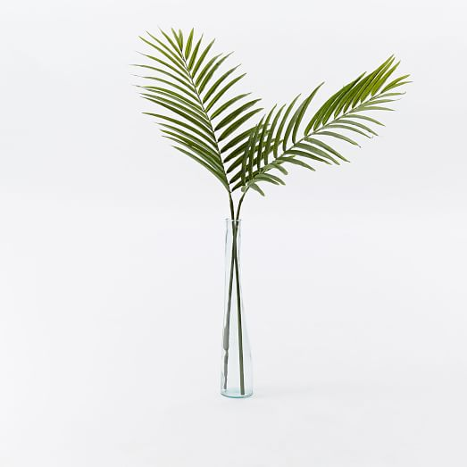 Two stems of palms in a clear glass vase.
