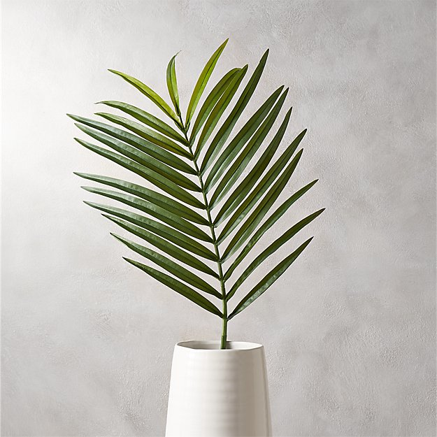A single stem palm in a white vase.