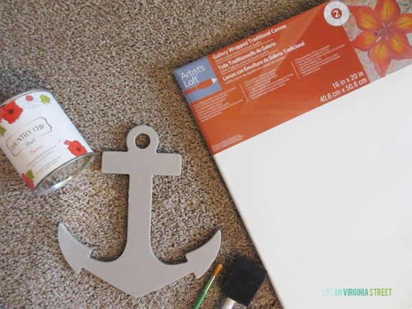 The anchor, canvas, and paint supplies laid out on the carpet.