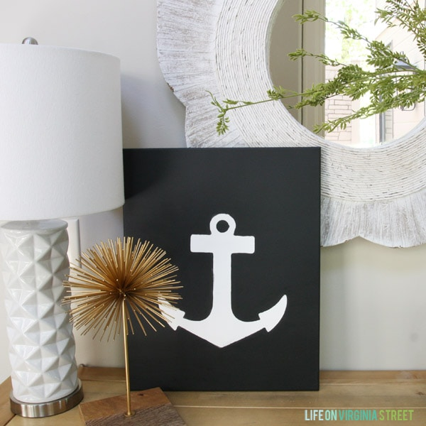 Anchor canvas art on the side table in the hallway with a white lamp beside it.