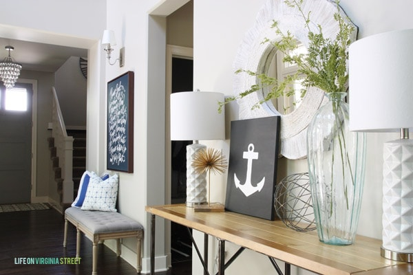 The anchor art on a wooden side table in hallway.
