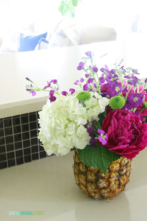 The fresh pineapple vase on the counter filled with flowers.