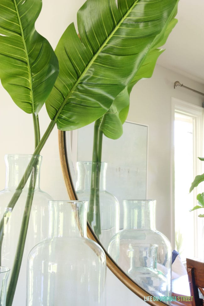 Banana leaves in beautiful glass bottles have a huge impact in this dining room makeover.