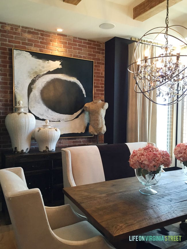 This gorgeous formal dining room features a red exposed brick wall, black walls, raw wood beams and a touch of glam with the orb chandelier.