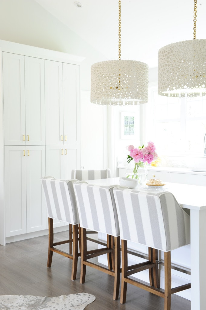 White and grey kitchen with striped barstools