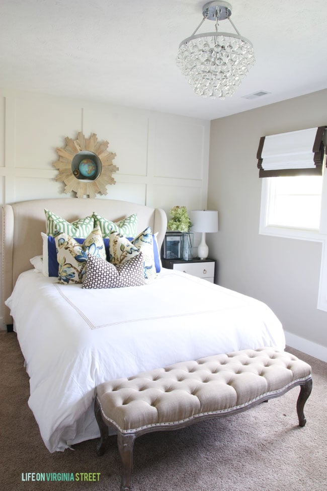 Guestroom wingback bed with white linens and green and blue accents.