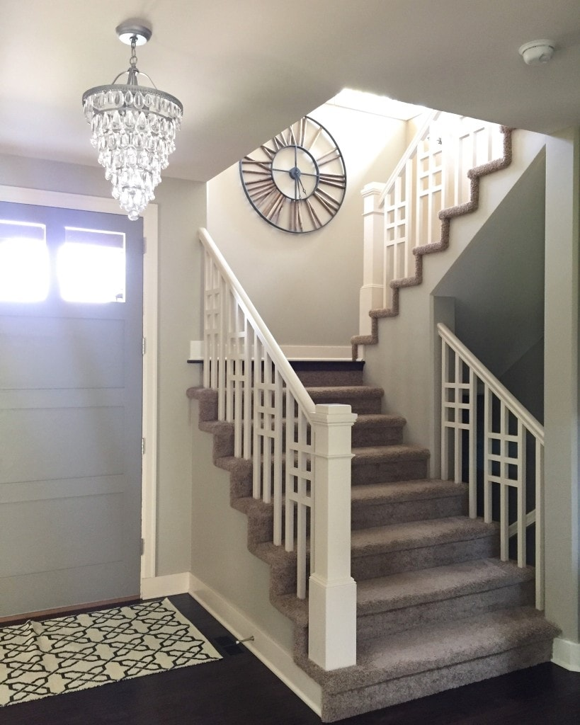 Gorgeous entryway with gray door, chandelier and beautiful railing on staircase.