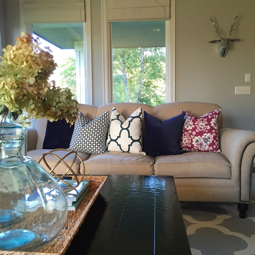 Fall living room with designer pillows in navy, white and plum.