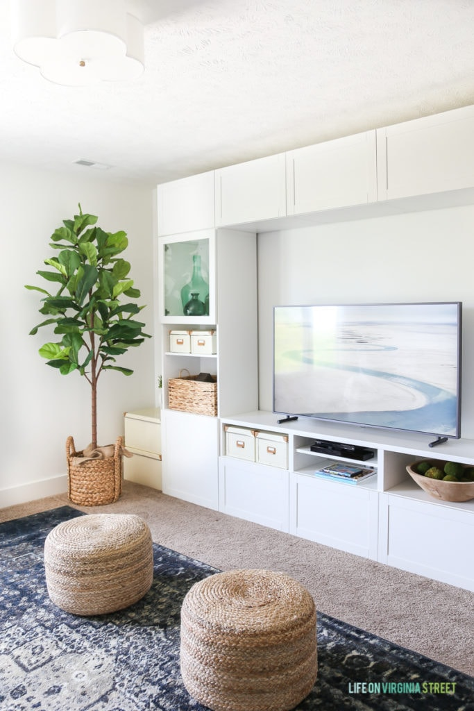 The tv room with neutral poufs and a white built in cabinet.