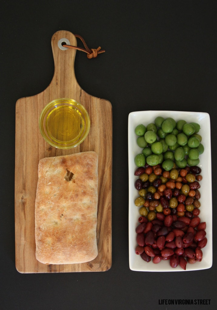 Bread board with bread on it, and olive oil for dipping, plus a tray of olives beside it.