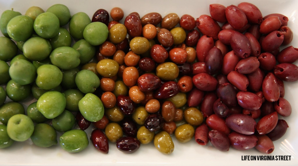 Mezzetta Olives in green, and red on a white plate.