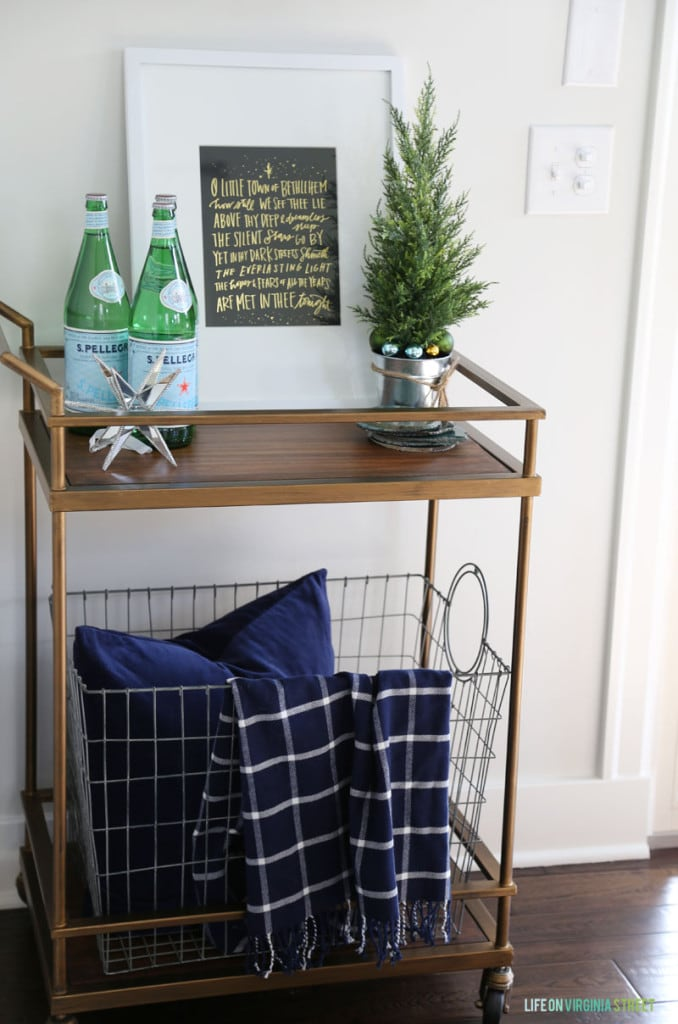 A brass and wood barcart decorated for Christmas with navy blue and green decor.