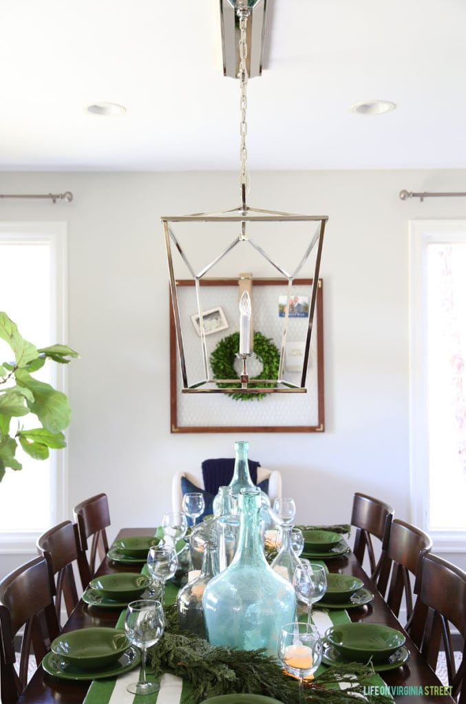 A Christmas dining room with green and white striped tablecloth and large recycled glass bottles.