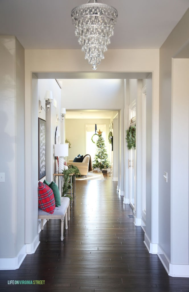 Christmas Entry Hallway with a crystal chandelier, dark hardwood floors, red plaid pillow and a view of a Christmas tree.