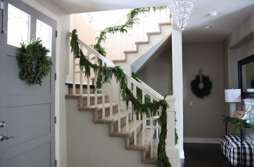 A beautiful Christmas entryway with fresh evergreen garland, a pinecone wreath, black and white buffalo check poufs, and a crystal chandelier.