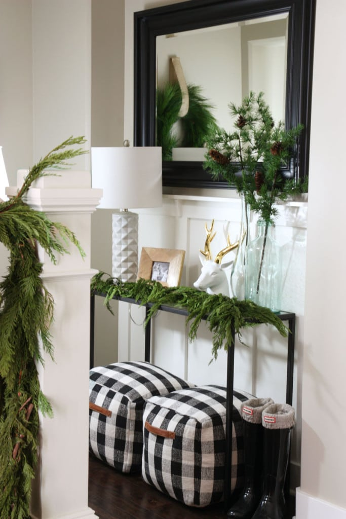 A darling Christmas entryway with a black iron console table, black and white buffalo check pouf ottomans, a black framed mirror, fresh garland swag, and black, white and green accents.