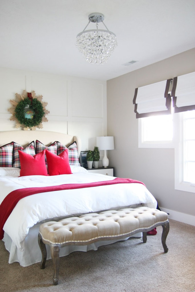 A Christmas guest bedroom with red velvet pillows, plaid pillows, a boxwood wreath, linen bench and a crystal chandelier.