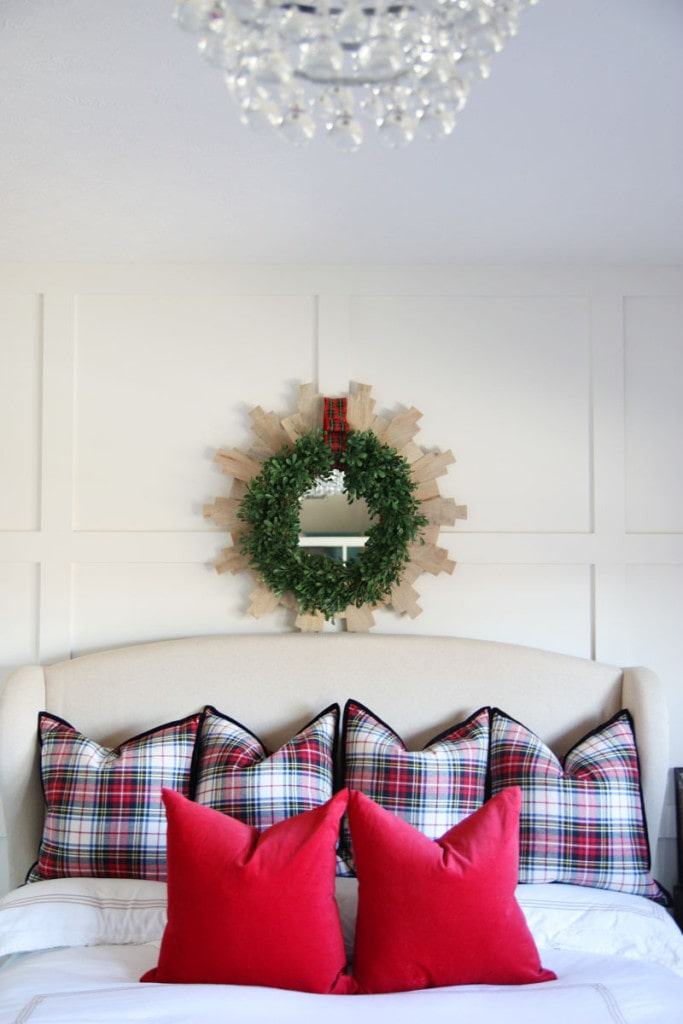 A Christmas guest bedroom with red velvet pillows, a linen headboard, plaid pillows and a boxwood wreath.