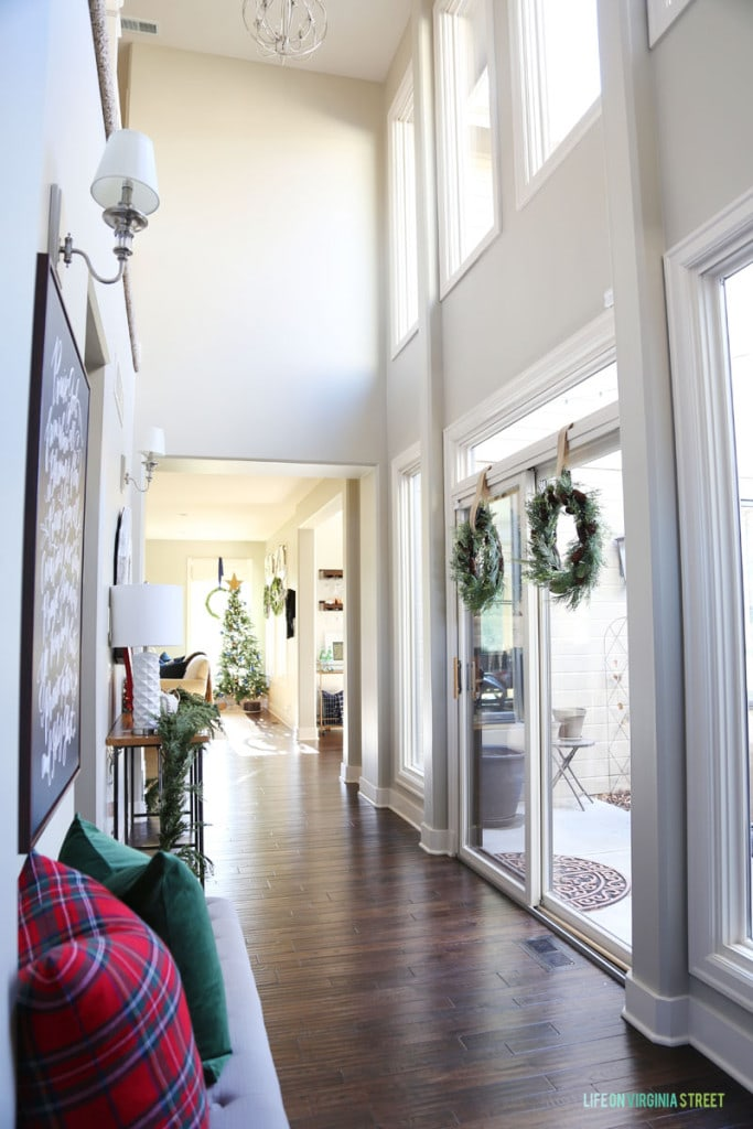 A Christmas hallway with wreaths hanging on the window and red plaid and green accents.