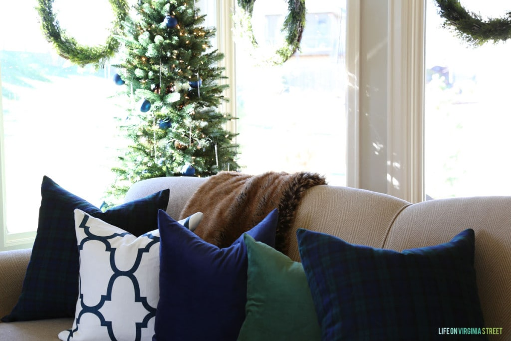 A combination of navy blue velvet, green velvet, and blue and white trellis pillows on a Christmas sofa.