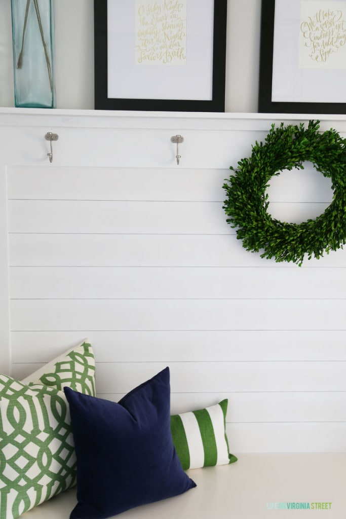 A Christmas mudroom with green trellis pillow, navy blue velvet pillow, a boxwood wreath, and Christmas hymn artwork.