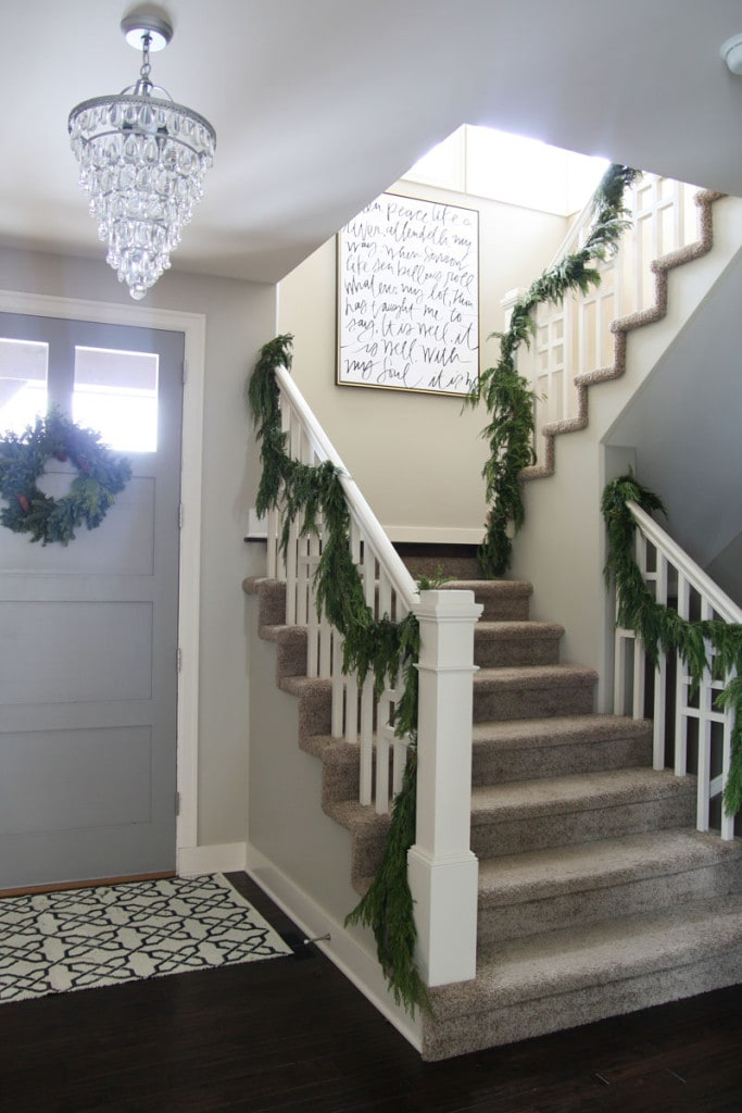 "A Christmas staircase with fresh greenery and a gorgeous ""It Is Well With My Soul"" canvas on the wall."