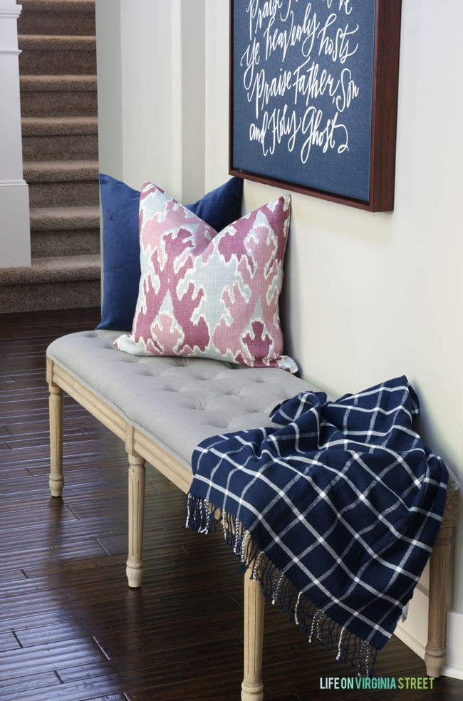 Fall Entryway with bench beside the wall and pink and blue pillows on it.