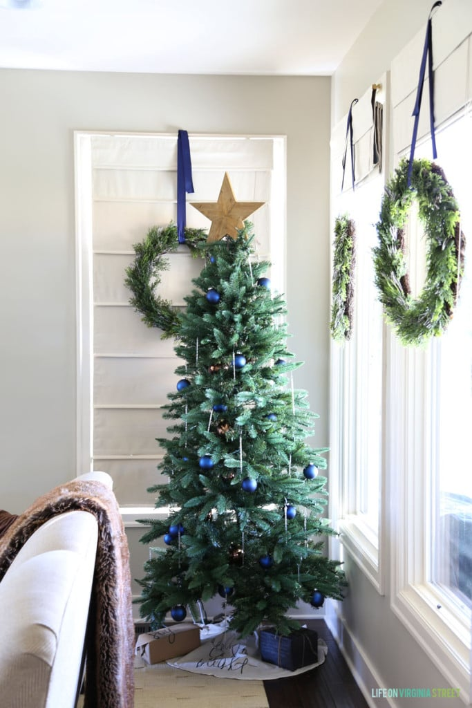 A Christmas tree with navy blue ornaments and glass icicles. I also love the wreaths hanging from the window with navy blue ribbon!