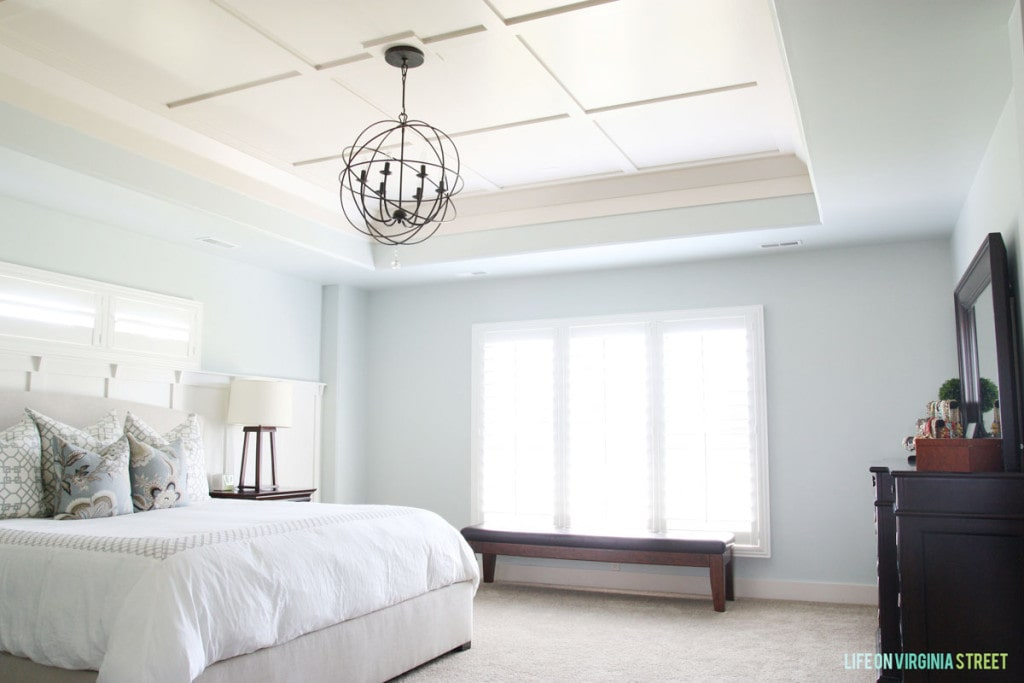 Light blue walls in bedroom with chandelier above white bed.