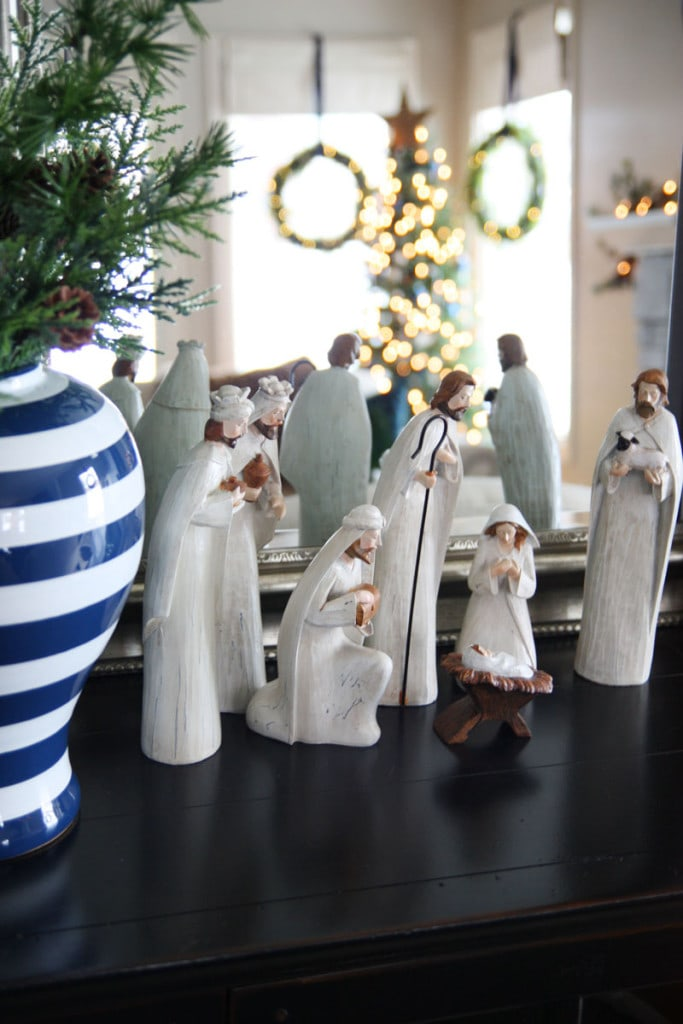 A wood nativity scene in a blue and white Christmas living room.
