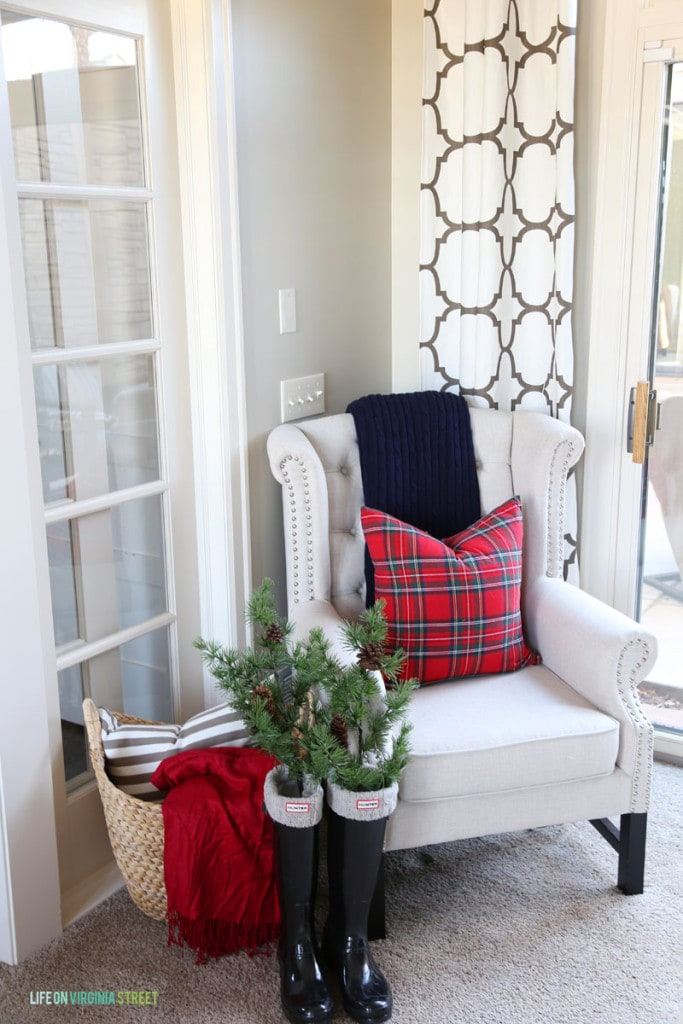 Office Christmas Chair with red plaid pillow, black glossy Hunter boots filled with greenery, and a trellis curtain panel.
